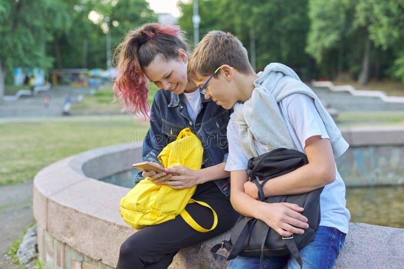 Retrato exterior de dois adolescentes de fala com smartphone imagem de stock royalty free