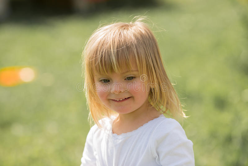 Retrato exterior de sorriso feliz do fim real louro caucasiano novo da menina dos povos do bebê imagens de stock royalty free