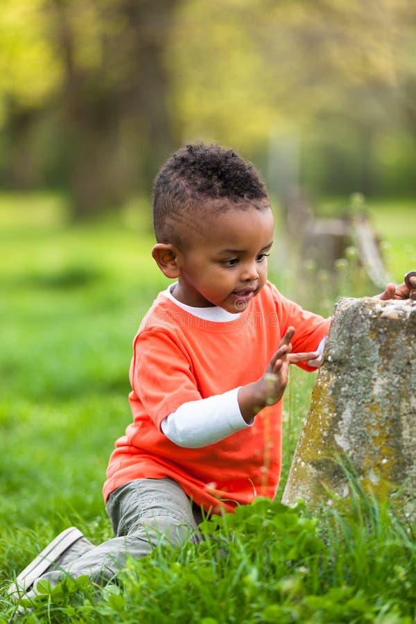 Retrato exterior de um menino preto pequeno novo bonito que joga o outsi imagens de stock royalty free