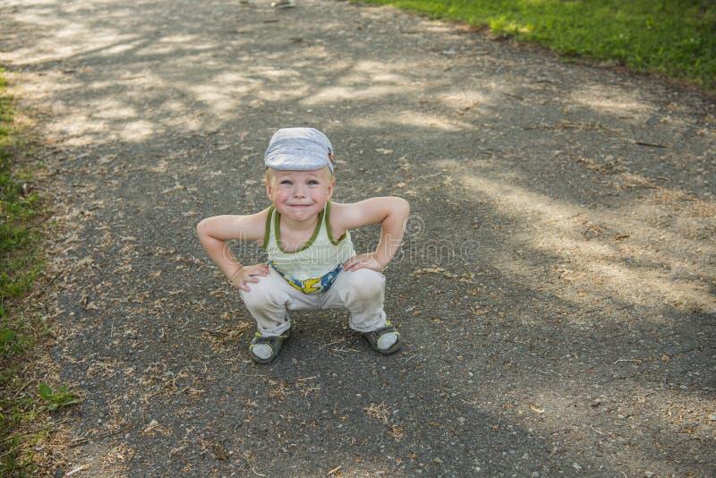 Retrato exterior de um rapaz pequeno bonito para cruzar a estrada Conceito da educação com uma criança imagens de stock