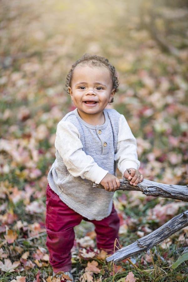Retrato exterior de um rapaz pequeno de sorriso bonito da raça misturada imagens de stock