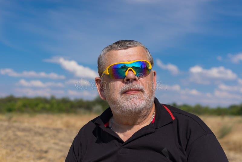 Retrato exterior de um sênior farpado nos óculos de sol contra o céu nebuloso azul imagem de stock royalty free
