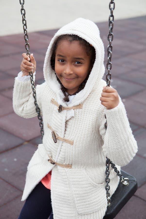Retrato exterior de uma menina preta nova bonito que joga com um balanço imagem de stock royalty free