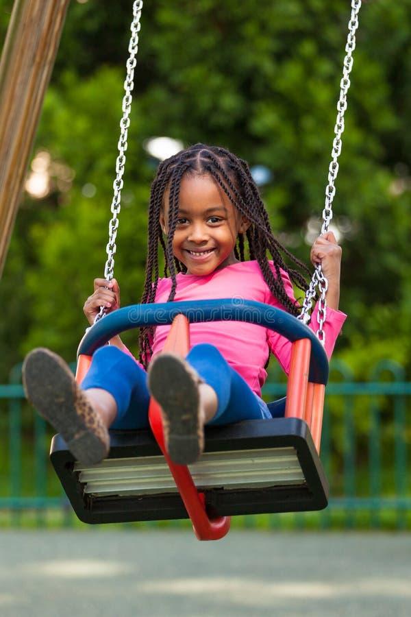 Retrato exterior de uma menina preta nova bonito que joga com um swin fotografia de stock royalty free