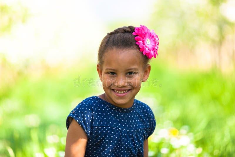 Retrato exterior de uma menina preta nova bonito que sorri - pe africano fotografia de stock