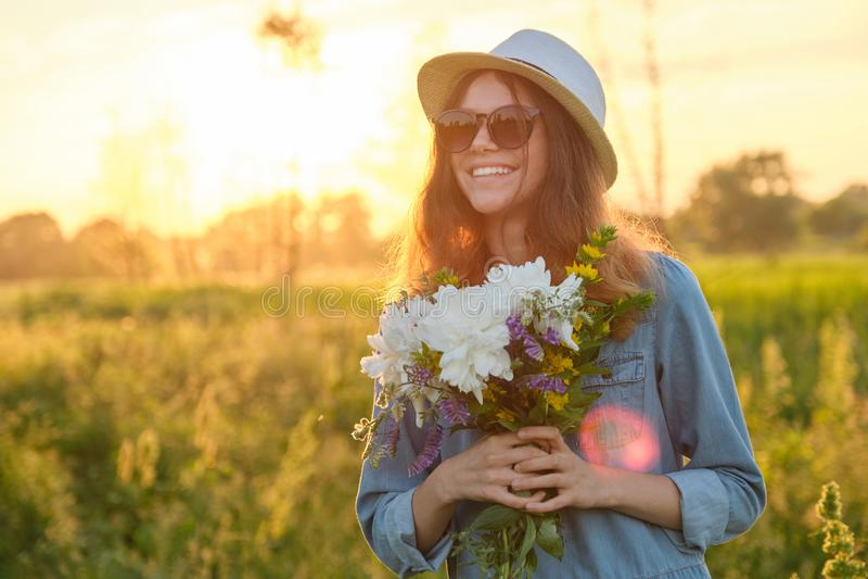 Retrato exterior de uma moça com flores em um prado, hora dourada imagens de stock