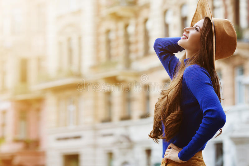 Retrato exterior de uma mulher de sorriso feliz bonita nova que levanta na rua Chapéu e roupa à moda vestindo modelo foto de stock