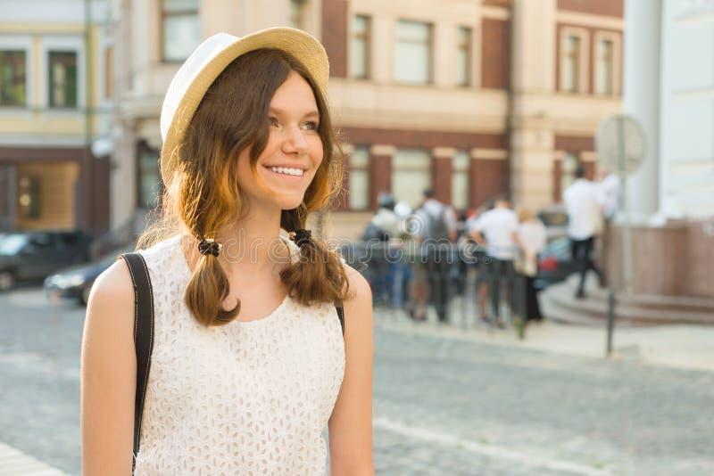 Retrato exterior do adolescente 13, 14 anos velhos, fundo da rua da cidade A menina bonita de sorriso romântica em um chapéu olha imagens de stock royalty free