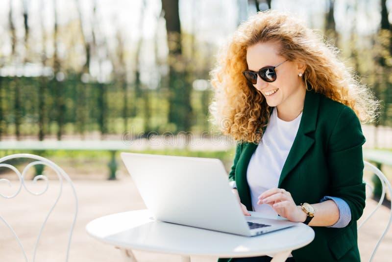 Retrato exterior do assento fêmea encaracolado novo atrativo na mesa no parque usando suas mensagens da escrita do portátil a seu fotos de stock
