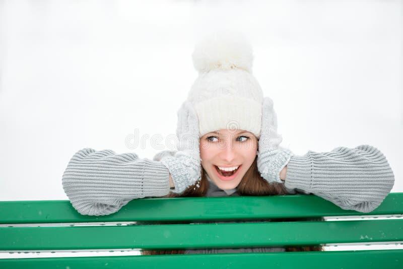 Retrato exterior do close-up da menina de sorriso feliz bonita nova, do chapéu feito malha à moda vestindo e das luvas do inverno imagem de stock royalty free