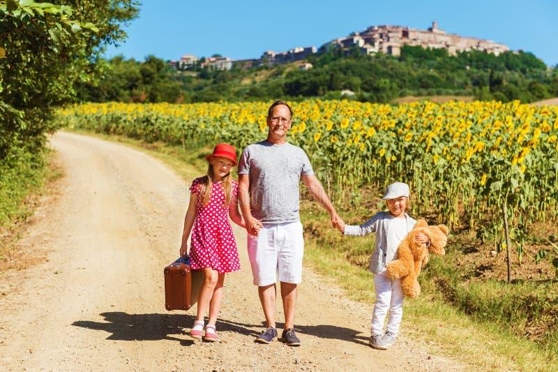 Retrato exterior do crianças engraçadas e o pai que anda abaixo da estrada foto de stock