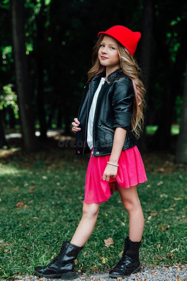 Retrato exterior do estilo de vida do adolescente à moda da menina no parque da cidade Criança bonita, vestindo imagens de stock