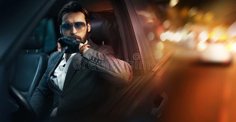 Retrato exterior do homem da forma que conduz um carro imagem de stock
