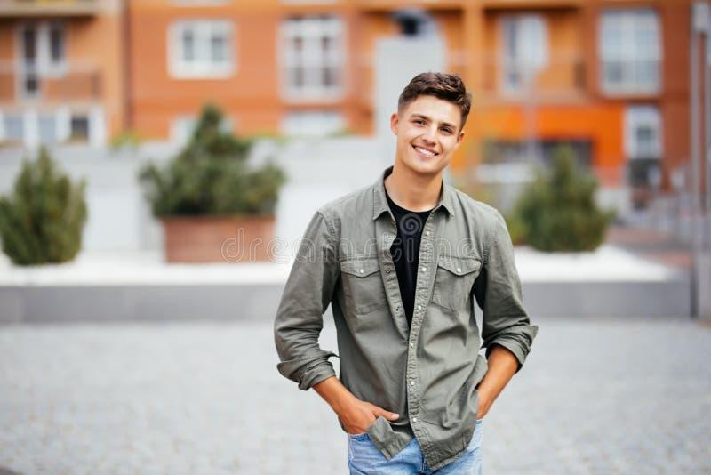 Retrato exterior do homem novo considerável que anda na rua, olhando a câmera e o sorriso imagens de stock