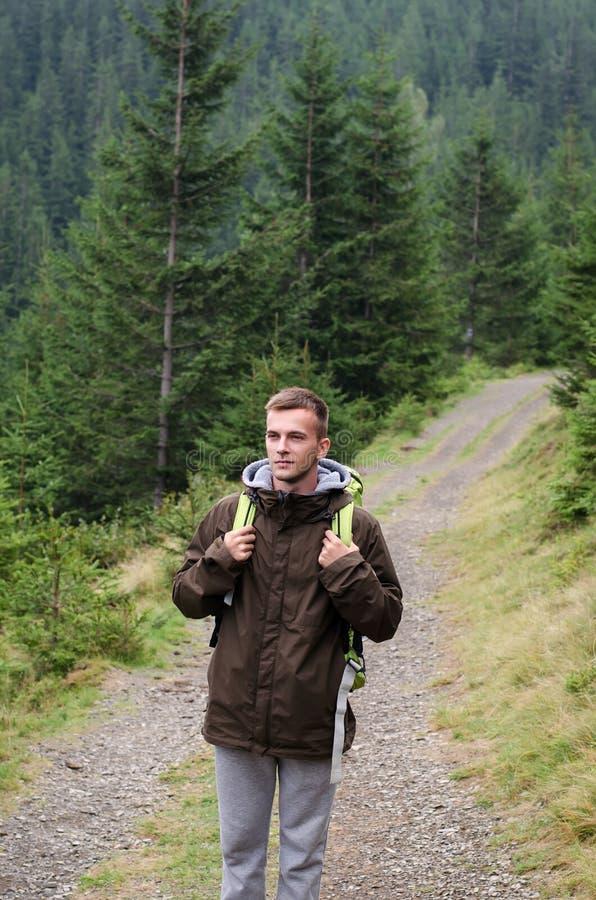 Retrato exterior do homem novo que caminha nas montanhas, retrato feliz de sorriso do homem do turista esporte extremo, equipamen imagem de stock royalty free