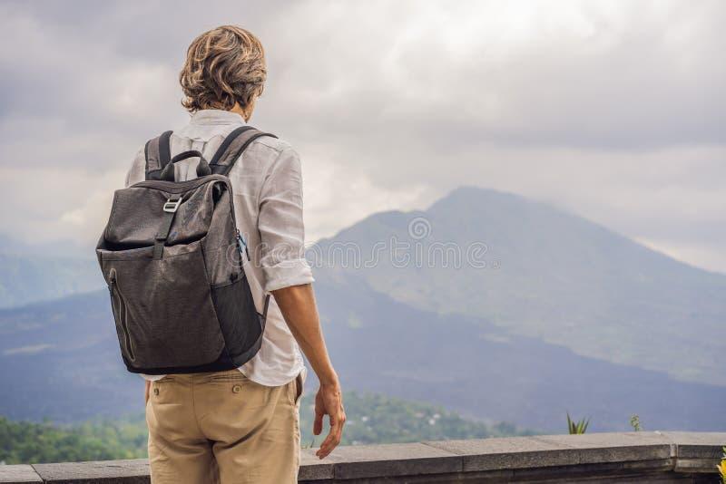 Retrato exterior do homem novo que olha no Mountain View do vulcão de Batur e de Agung na manhã de Kintamani, Bali fotografia de stock royalty free