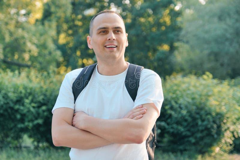 Retrato exterior do homem positivo de sorriso maduro Homem seguro no t-shirt branco com a trouxa com m?os dobradas fotos de stock royalty free