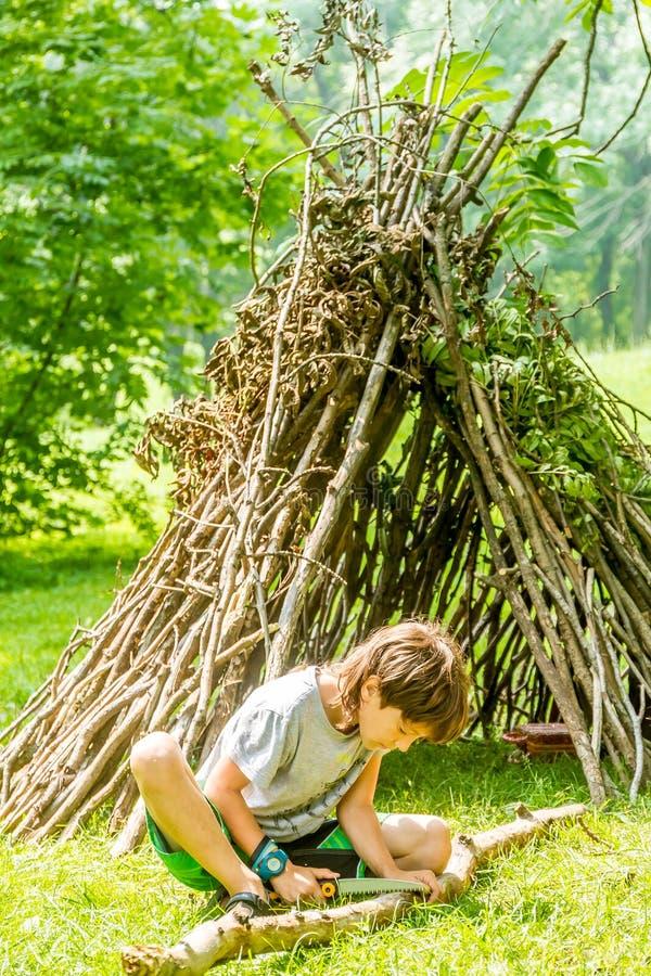 Retrato exterior do menino da criança que joga ao lado da cabana de madeira h da vara imagens de stock