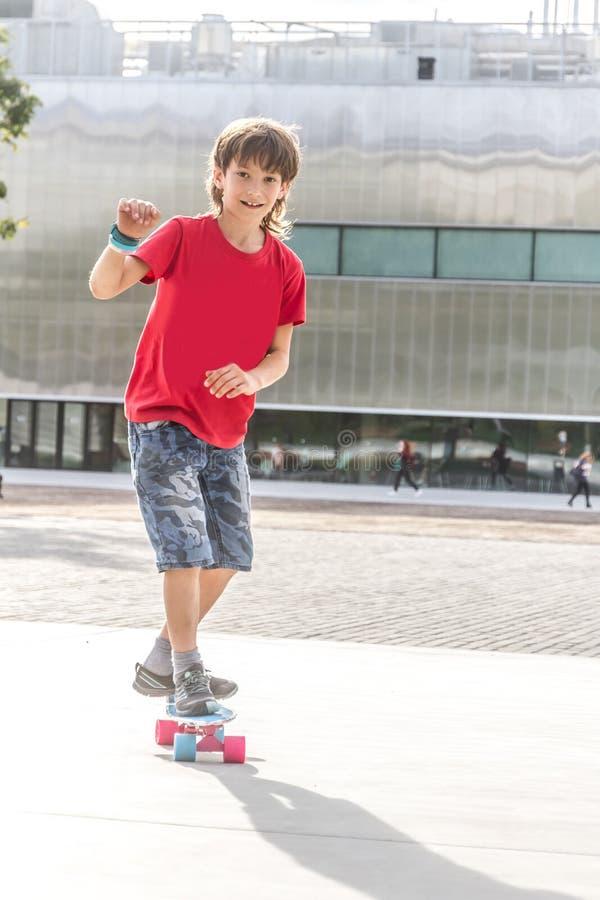 Retrato exterior do menino de sorriso novo do adolescente que monta o modo curto fotografia de stock royalty free