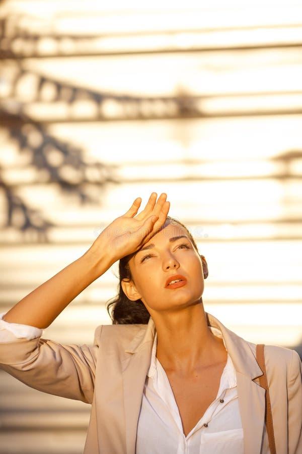 Retrato exterior do verão da moça no calor de sofrimento do sol do terno Mulher de negócio bonita na rua no dia quente foto de stock royalty free