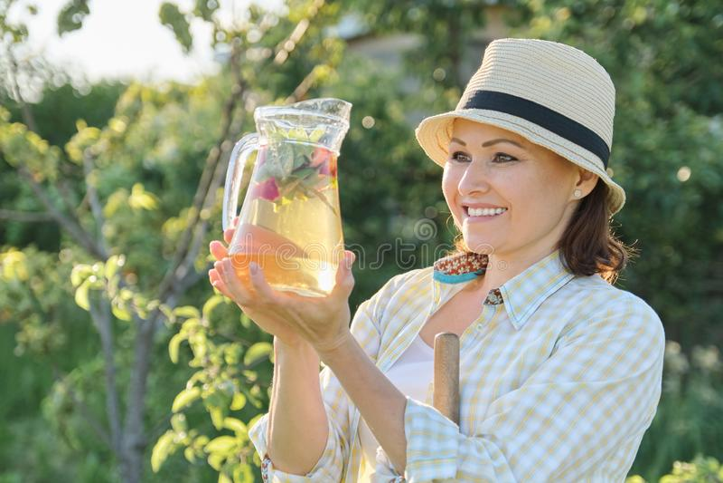 Retrato exterior do verão da mulher com a bebida natural feita das ervas da hortelã da morango, jardinagem da mulher foto de stock