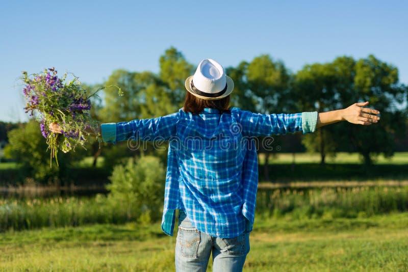 Retrato exterior do verão da mulher com o ramalhete dos wildflowers, chapéu de palha A vista do traseiro, fêmea levantou sua mão imagem de stock