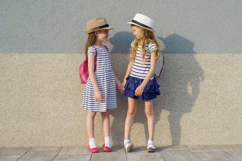 Retrato exterior do verão de duas namoradas felizes 7,8 anos no perfil que fala e que ri Meninas nos vestidos listrados, chapéus  imagem de stock royalty free