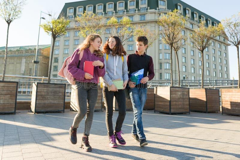 Retrato exterior dos estudantes adolescentes com trouxas que andam e que falam imagem de stock royalty free