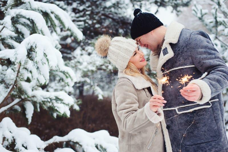 Retrato exterior dos pares românticos felizes que comemoram o Natal com fogos-de-artifício ardentes imagens de stock royalty free
