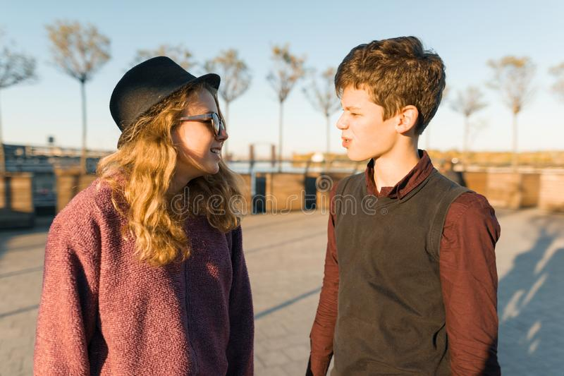 Retrato exterior dos um par menino novo e meninas que olham se, adolescentes de sorriso na luz do por do sol, hora dourada fotos de stock
