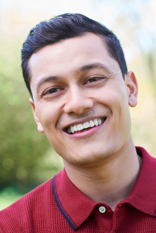 Retrato exterior principal e dos ombros do homem novo de sorriso imagem de stock