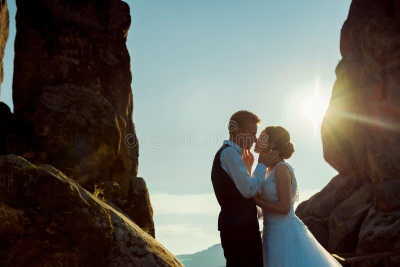 Retrato exterior romântico dos pares novos bonitos do recém-casado que vão beijar durante o por do sol imagem de stock royalty free
