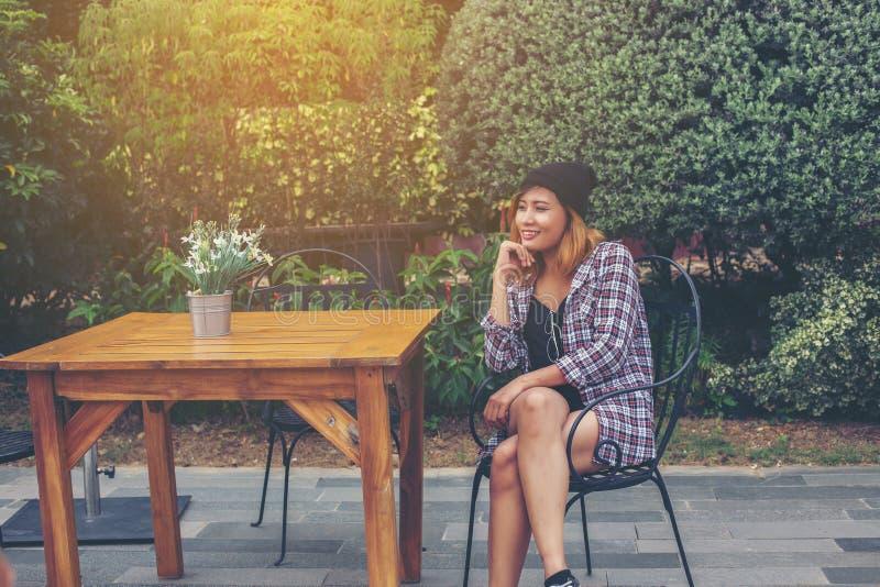 Retrato externo de uma jovem hipster sentada sozinha no velho café da cidade e esperando o namorado vestindo roupas peladas e foto de stock
