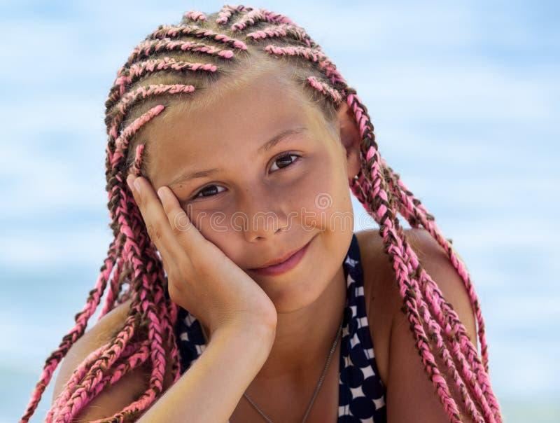 Retrato facial de uma menina bonita com cadeado africano cor-de-rosa, olhando para a câmera com sorriso, olhos castanhos imagens de stock royalty free