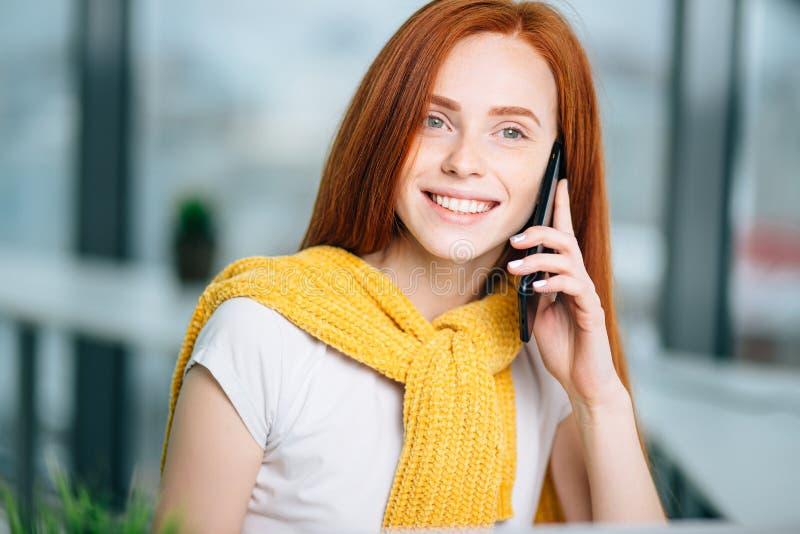 Retrato facial del primer de la mujer feliz del pelirrojo en llamada de teléfono móvil foto de archivo libre de regalías