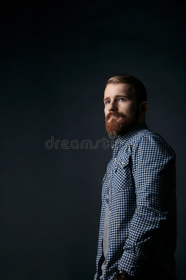 Retrato farpado vermelho pensativo do estúdio do homem no fundo escuro fotos de stock