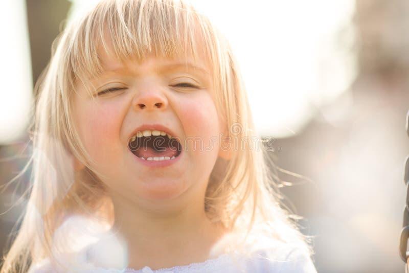 Retrato fazendo caretas exterior de sorriso feliz do fim real louro caucasiano novo da menina dos povos do bebê fotografia de stock