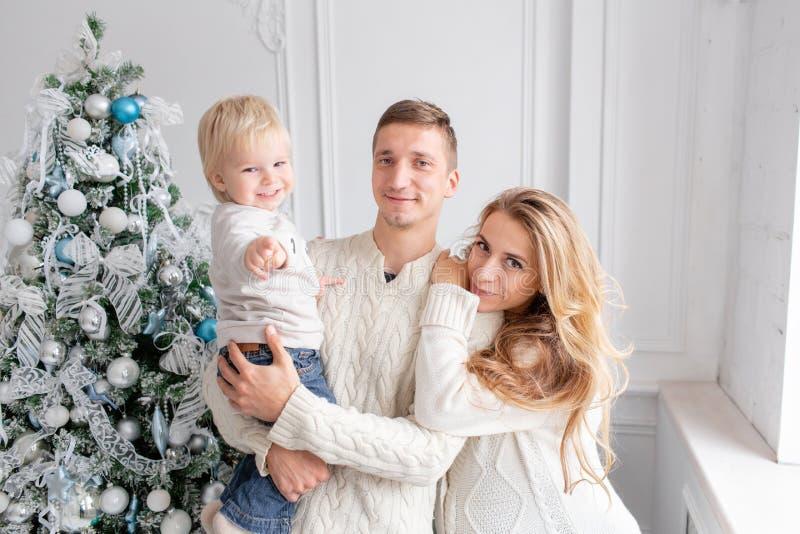Retrato feliz da família na casa - gene, mãe grávida e seu filho pequeno Ano novo feliz Árvore de Natal decorada imagem de stock