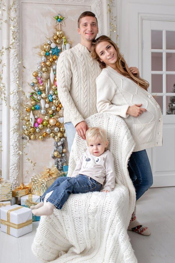 Retrato feliz da família na casa - gene, mãe grávida e seu filho pequeno Ano novo feliz Árvore de Natal decorada fotos de stock