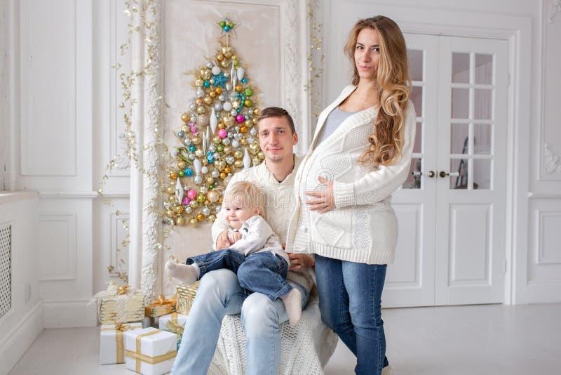 Retrato feliz da família na casa - gene, mãe grávida e seu filho pequeno Ano novo feliz Árvore de Natal decorada foto de stock