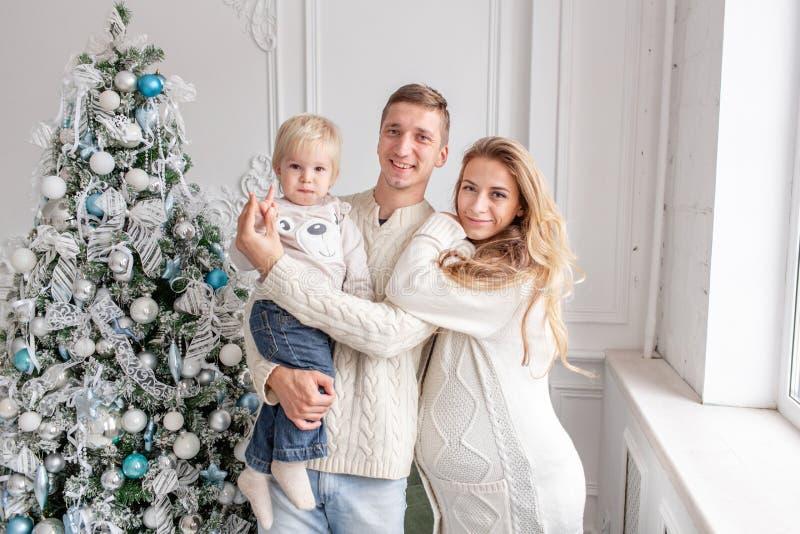 Retrato feliz da família na casa - gene, mãe grávida e seu filho pequeno Ano novo feliz Árvore de Natal decorada foto de stock royalty free