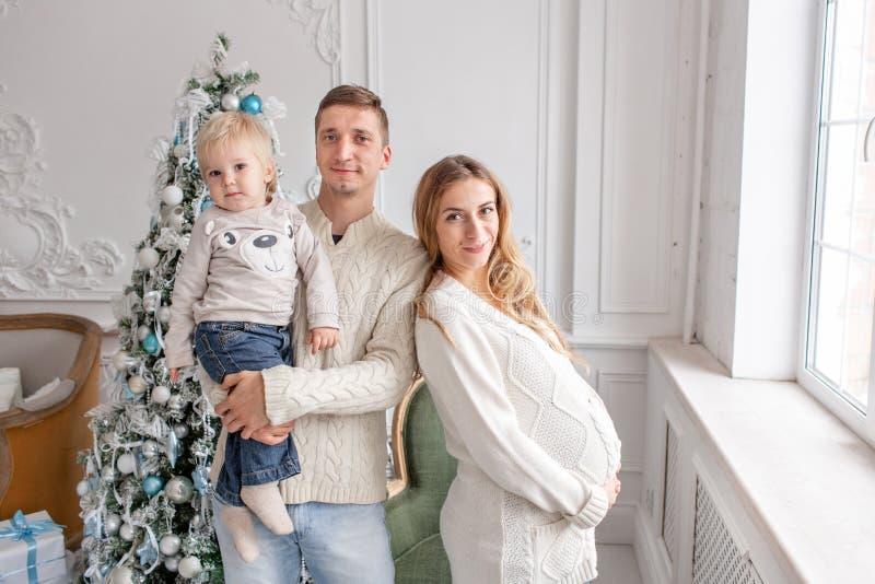 Retrato feliz da família na casa - gene, mãe grávida e seu filho pequeno Ano novo feliz Árvore de Natal decorada imagens de stock royalty free