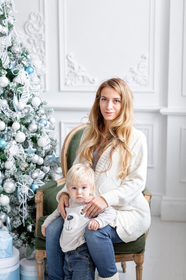 Retrato feliz da família na casa - a mãe grávida dos jovens abraça seu filho pequeno Ano novo feliz Árvore de Natal decorada imagens de stock