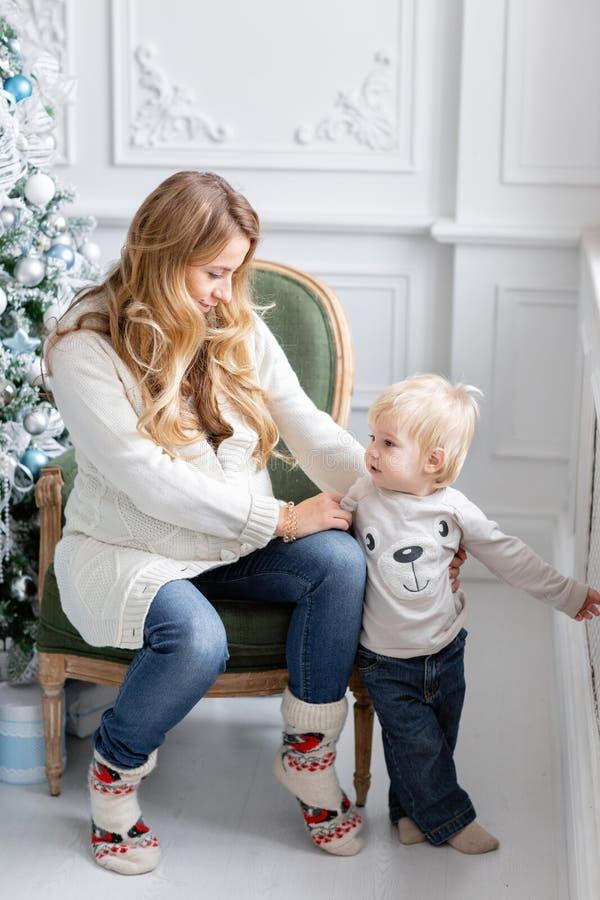 Retrato feliz da família na casa - a mãe grávida dos jovens abraça seu filho pequeno Ano novo feliz Árvore de Natal decorada foto de stock royalty free