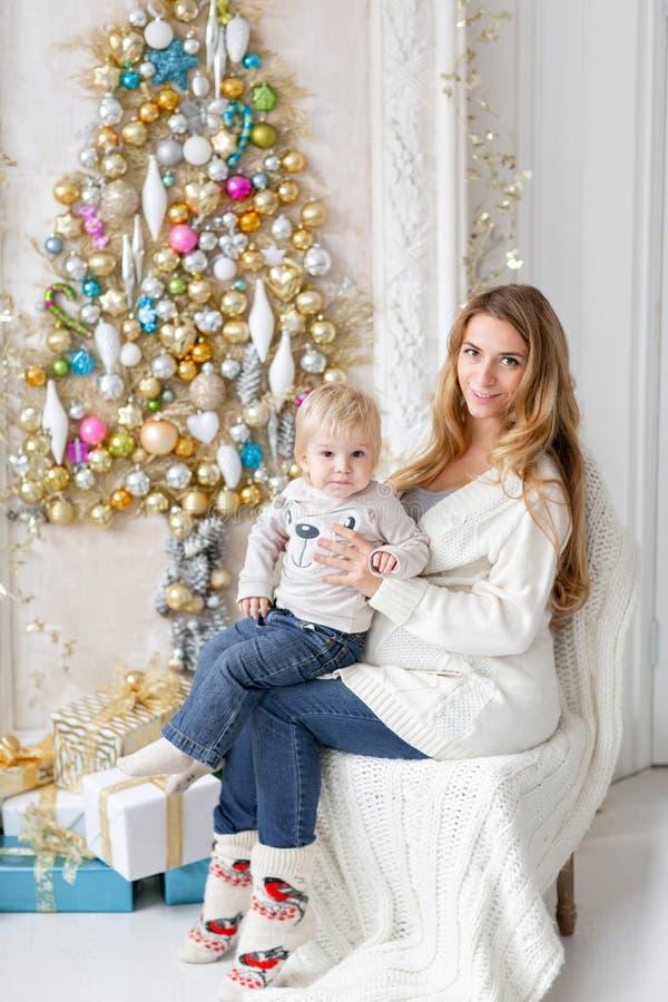Retrato feliz da família na casa - a mãe grávida dos jovens abraça seu filho pequeno Ano novo feliz Árvore de Natal decorada fotos de stock