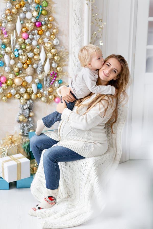 Retrato feliz da família na casa - a mãe grávida dos jovens abraça seu filho pequeno Ano novo feliz Árvore de Natal decorada fotografia de stock royalty free