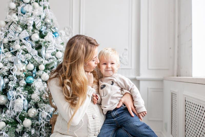 Retrato feliz da família na casa - a mãe grávida dos jovens abraça seu filho pequeno Ano novo feliz Árvore de Natal decorada imagem de stock