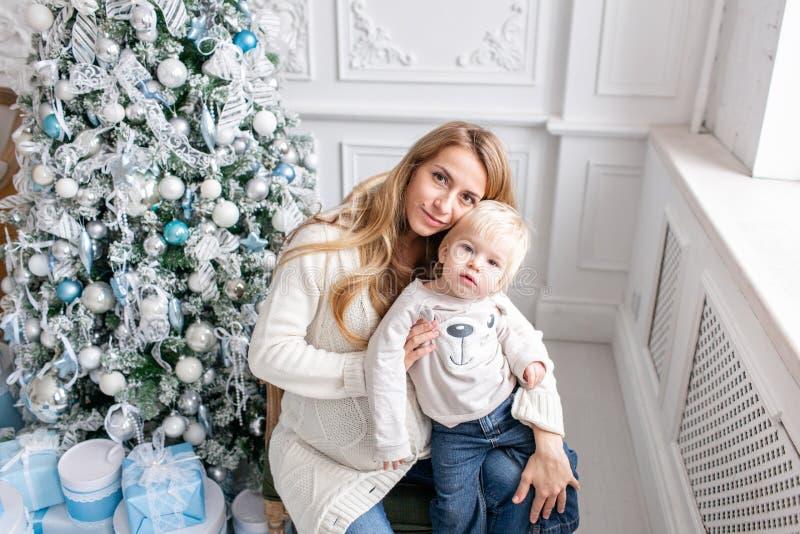 Retrato feliz da família na casa - a mãe grávida dos jovens abraça seu filho pequeno Ano novo feliz Árvore de Natal decorada foto de stock