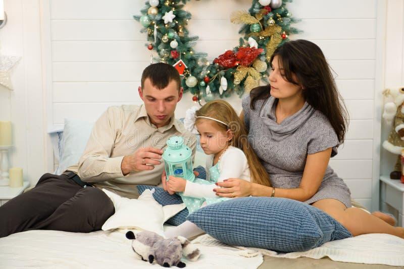 Retrato feliz da família no Natal, na mãe, no pai e na criança sentando-se na cama e iluminando uma vela em casa, chritmas foto de stock royalty free