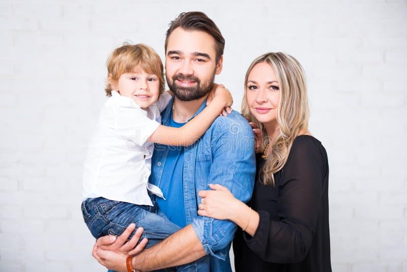 Retrato feliz da família - par com o filho pequeno sobre o branco foto de stock royalty free